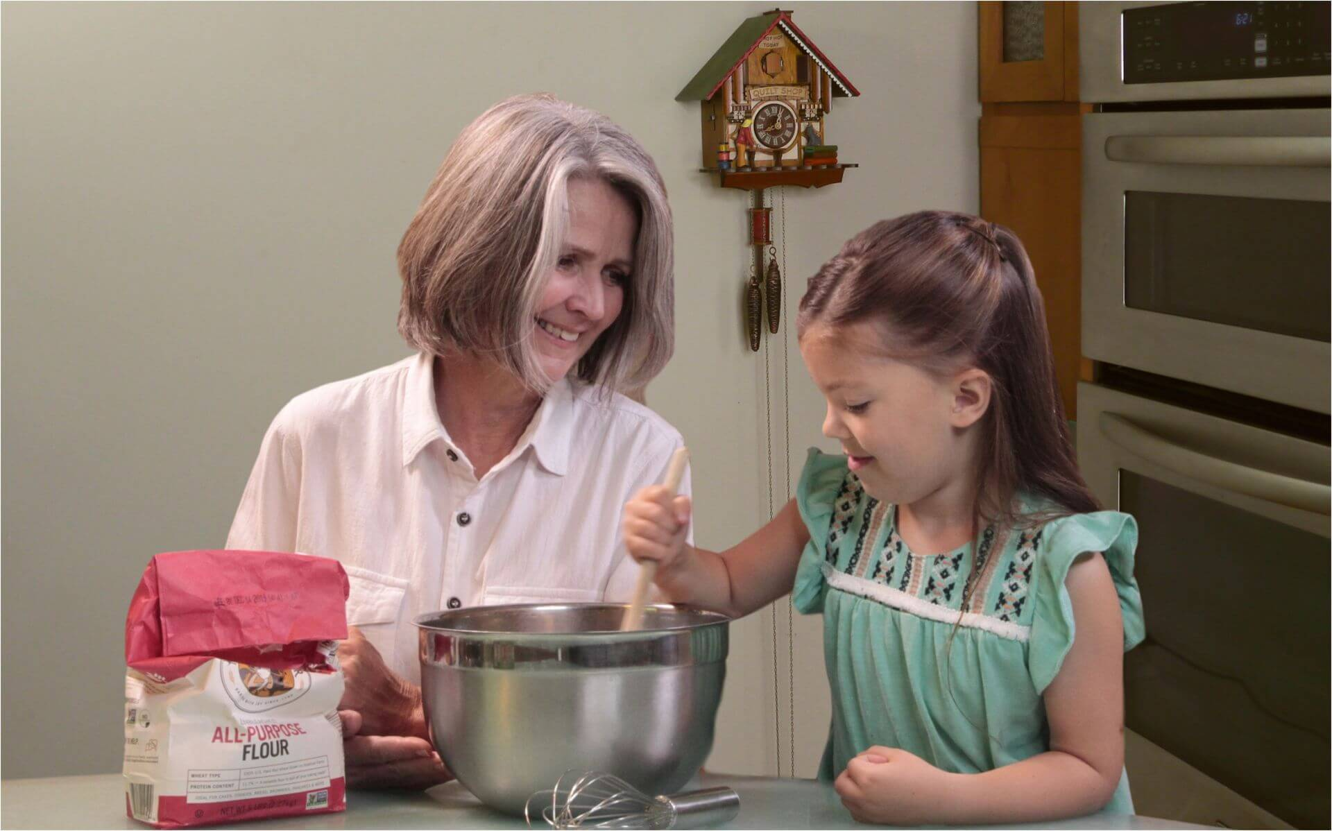 Grandmother and girl baking with cuckoo clock hanging on wall in kitchen